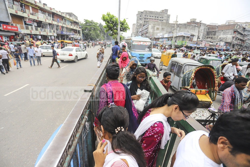 Pedestrians sneaking through a fence raised to stop them from crossing the street in New Market area of Dhaka on Friday . Photo: Asif Mahmud Ove
