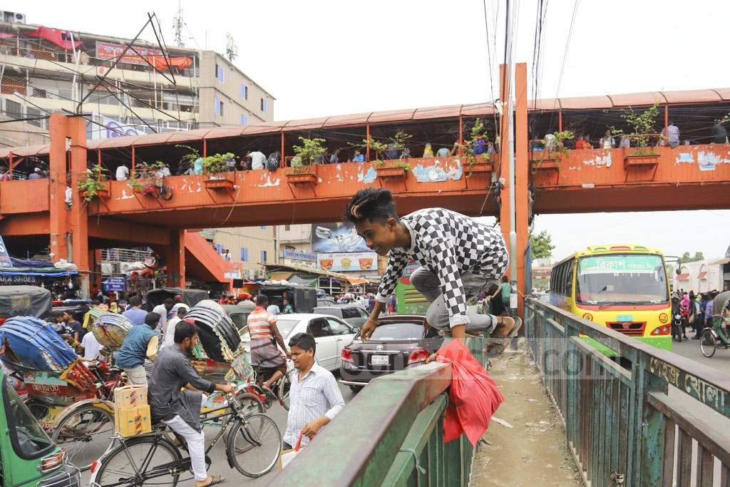 Pedestrians showing athletism to climb fences on road-dividers to cross a street in the New Market area of Dhaka on Friday, even though a footbridge is only a few feet away. Photo: Asif Mahmud Ove