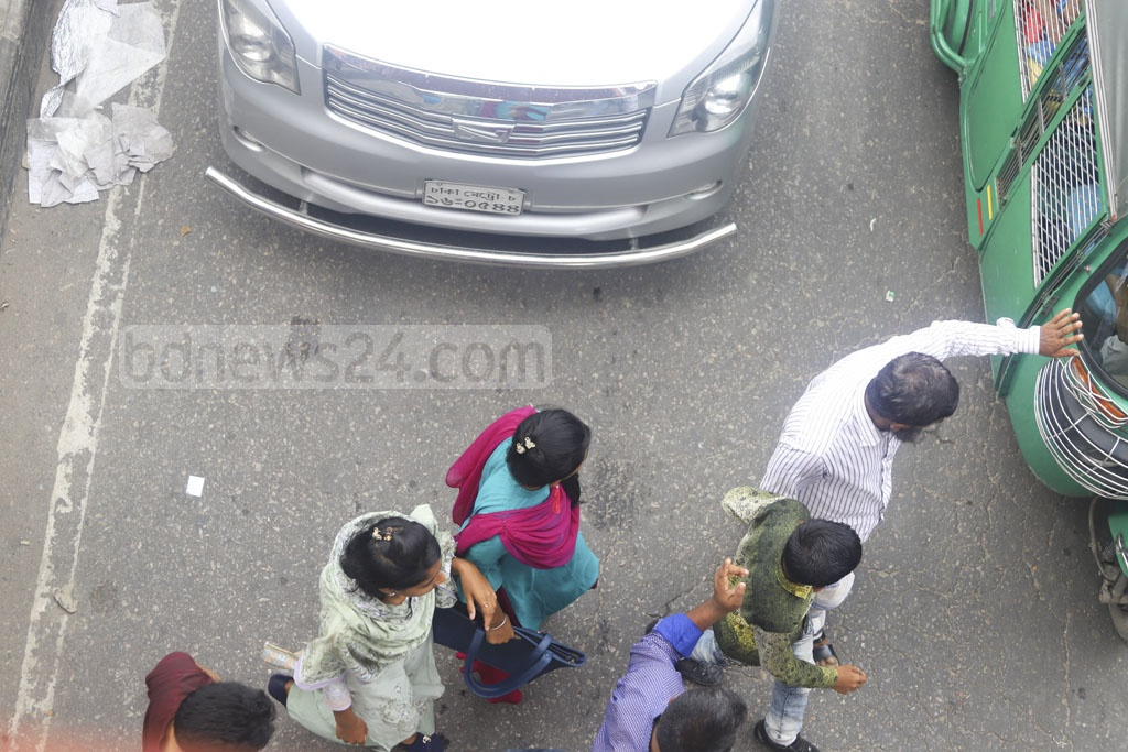 This photo of jaywalkers finding there way through vehicles to cross the street in the New Market area of Dhaka was taken from a footbridge on Friday. Photo: Asif Mahmud Ove