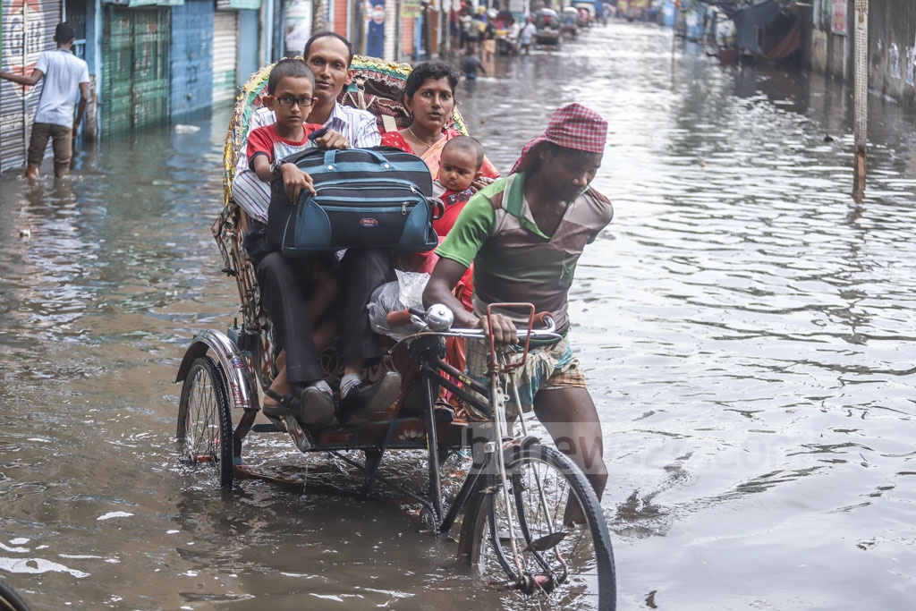 People take a rickshaw ride on the street from Sayedabad Bus Terminal to Janapath Sarak in Dhaka as it goes under knee-deep water after Saturday rains. Photo: Abdullah Al Momin