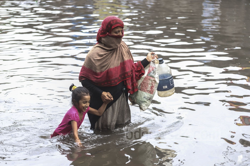 Women wade through knee-deep water on a street from Sayedabad Bus Terminal to Janapath Sarak in Dhaka to collect drinking water after Saturday rains. Photo: Abdullah Al Momin