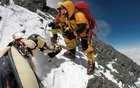 File - Sherpas work to pry the body of Goutam Ghosh from the ice on Mount Everest in May 2017. Two mountain climbers died near the top of Mount Everest in 2016. Their bodies lay frozen there for a year. Then a perilous journey began to bring them home. (Dawa Finjhok Sherpa/Seven Summit Treks/The New York Times)