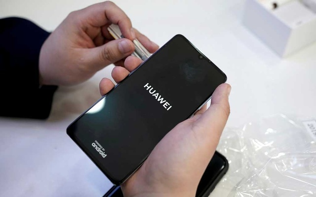 FILE PHOTO: A salesman turns on a new Huawei P30 smartphone for a customer after Huawei's P30 and P30 Pro went on sale at a Huawei store in Beijing, China, April 11, 2019. Reuters
