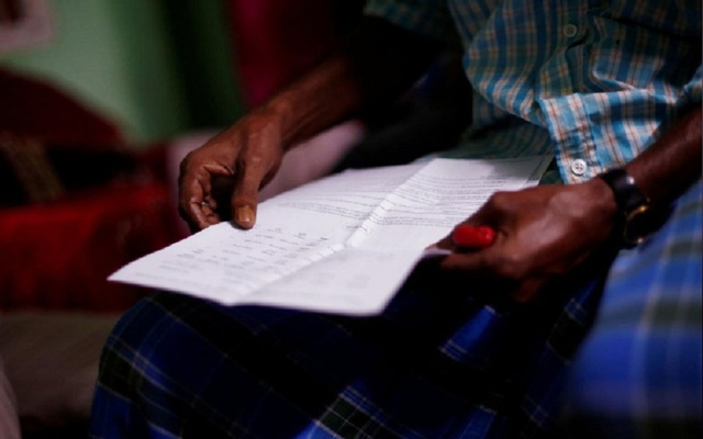 File Photo: A man holds the draft list of the National Register of Citizens (NRC) of his family in Dhubri district, in the northeastern state of Assam, India August 2, 2018. Picture taken August 2, 2018. REUTERS/Adnan Abidi
