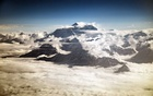 FILE -- Mount Everest peeks above the clouds on a sightseeing flight, in Kathmandu, Nepal, May 16, 2017. In the last few seasons, climbers say they have seen more bodies lying on the icy slopes of Everest than ever before. Both the climbers and the Nepalese government believe this is the grim result of global warming. (Josh Haner/The New York Times)