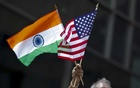 FILE PHOTO: A man holds the flags of India and the US while people take part in the 35th India Day Parade in New York August 16, 2015. Reuters
