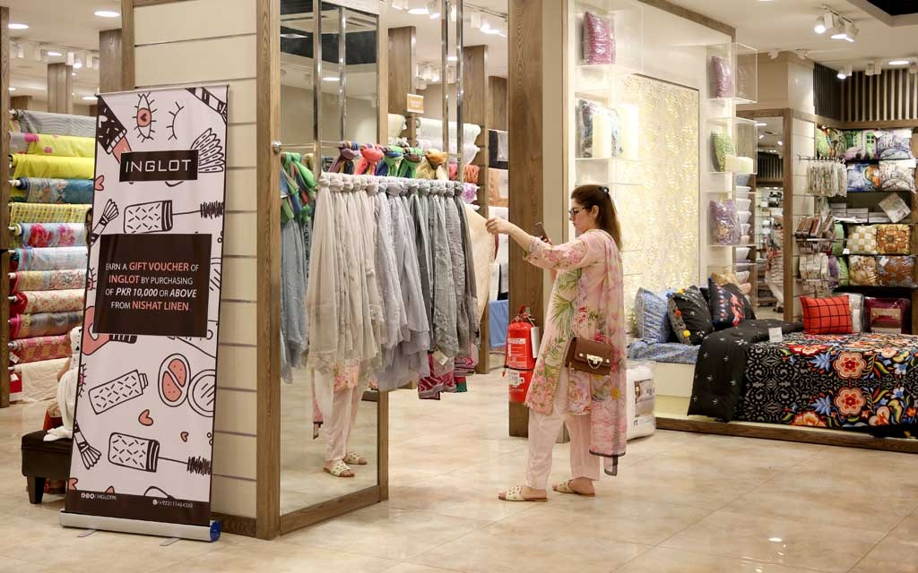 A woman takes a photo of textiles while shopping at The Centaurus mall, ahead of Muslim holiday of Eid al-Fitr, which marks the end of the holy fasting month of Ramadan in Islamabad, Pakistan May 22, 2019. REUTERS/Saiyna Bashir