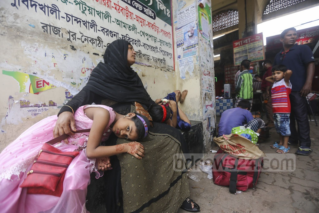 A tireless mother waits for a bus as her two children lie on her lap. Photo: Mahmud Zaman Ovi