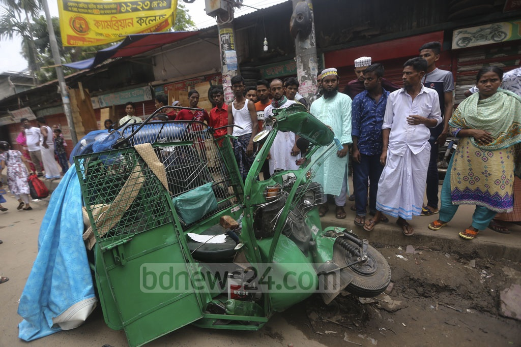 An autorickshaw is crushed during an alleged race between two buses on the road near Bangla School in Dhaka's Mirpur Section No 11 on Thursday injuring three people. Photo: Mahmud Zaman Ovi