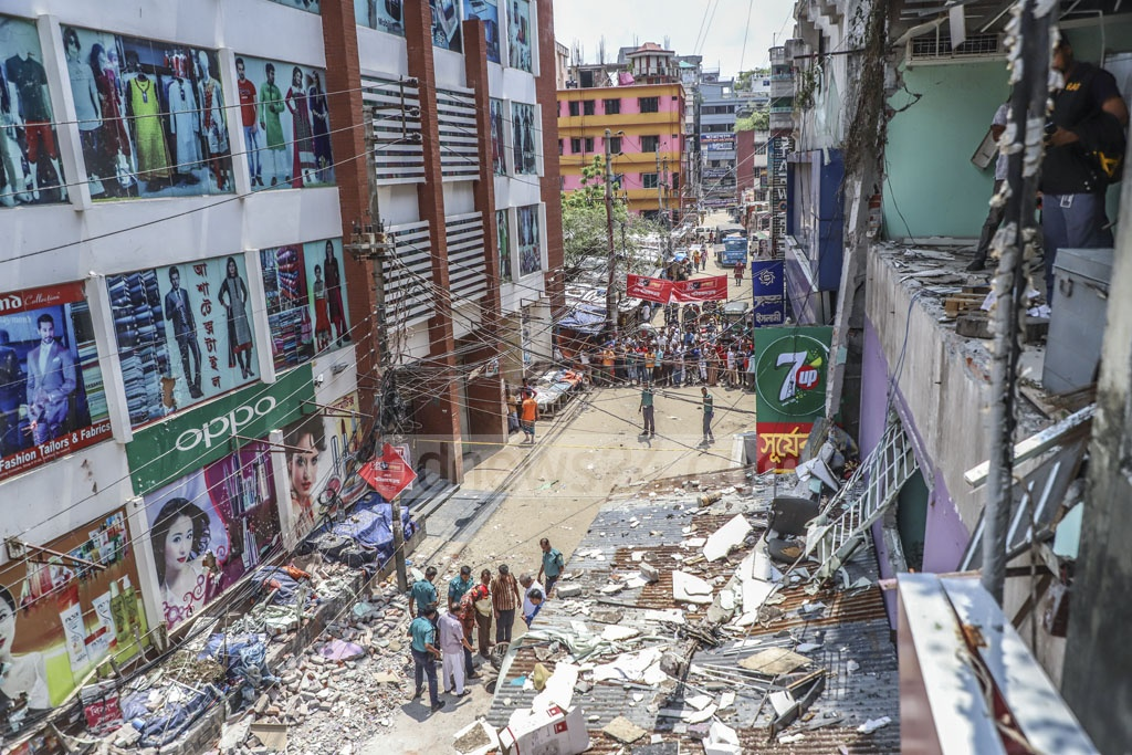 A pedestrian died and four others were injured when a wall from a commercial building in Dhaka's Shonir Akhra collapsed and fell on them after an AC compressor on the third floor exploded on Monday. Photo: Abdullah Al Momin