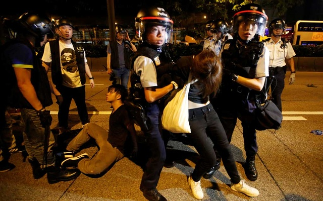 Police officers detain protesters during a protest to demand authorities scrap a proposed extradition bill with China, on Gloucester Road in Hong Kong, China Jun 10, 2019. REUTERS