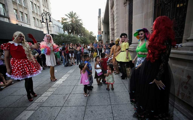 Participants dressed in drag dance along with children during the