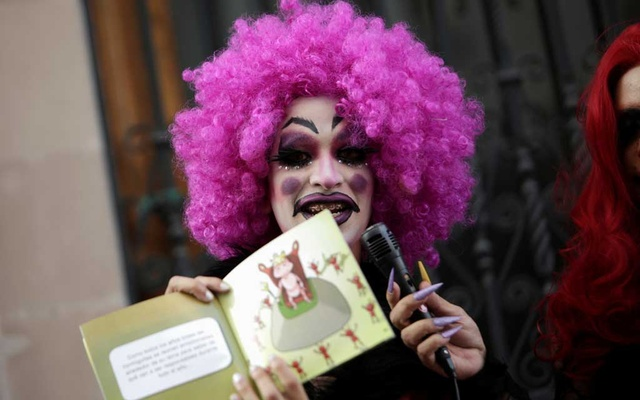 File Photo: A participant dressed in drag shows a book during the