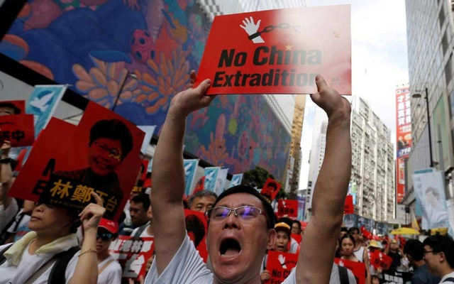FILE PHOTO: A demonstrator holds up a sign during a protest to demand authorities scrap a proposed extradition bill with China, in Hong Kong, China Jun 9, 2019. REUTERS