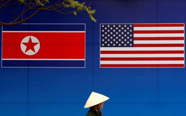 FILE PHOTO: A person walks past a banner showing North Korean and US flags ahead of the North Korea-US summit in Hanoi, Vietnam, Feb 25, 2019. REUTERS/Kim Kyung-Hoon/File Photo