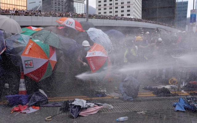 Protesters are hit by police water cannon during a demonstration against a proposed extradition bill in Hong Kong, China June 12, 2019. REUTERS/Tyrone Siu