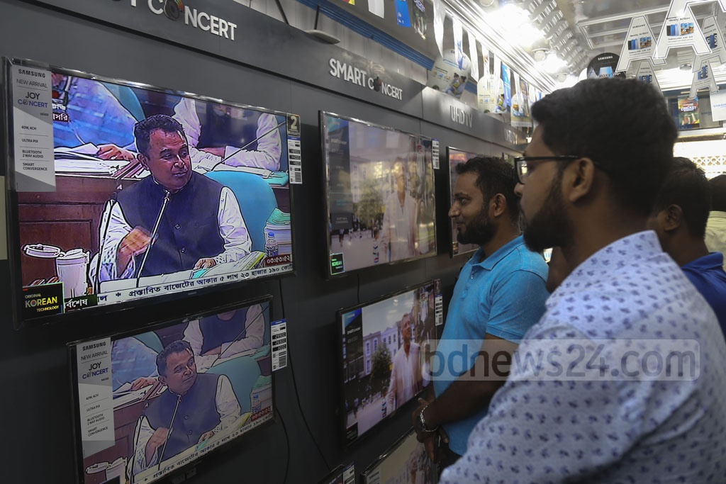 The public keenly follow what goods and services are going to cost more or less when the national budget is unveiled. They watched Finance Minister AHM Mustafa Kamal on TV in a store at Stadium Market on Thursdayas he gave his budget speech in parliament. Photo: Mahmud Zaman Ovi