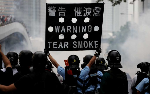 Police officer holds a sign during a demonstration against a proposed extradition bill in Hong Kong, China Jun 12, 2019. REUTERS