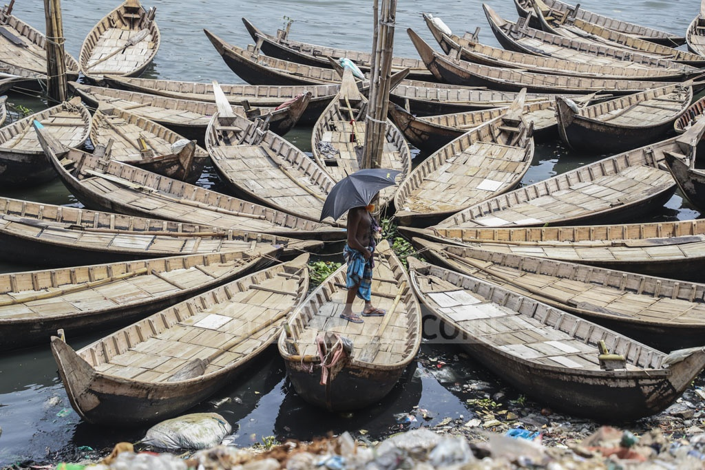 Small wooden boats are docked on the Buriganga river bank due to a lack of passengers. This photo was taken at Dhaka's Kamrangirchar on Saturday. Photo: Abdullah Al Momin