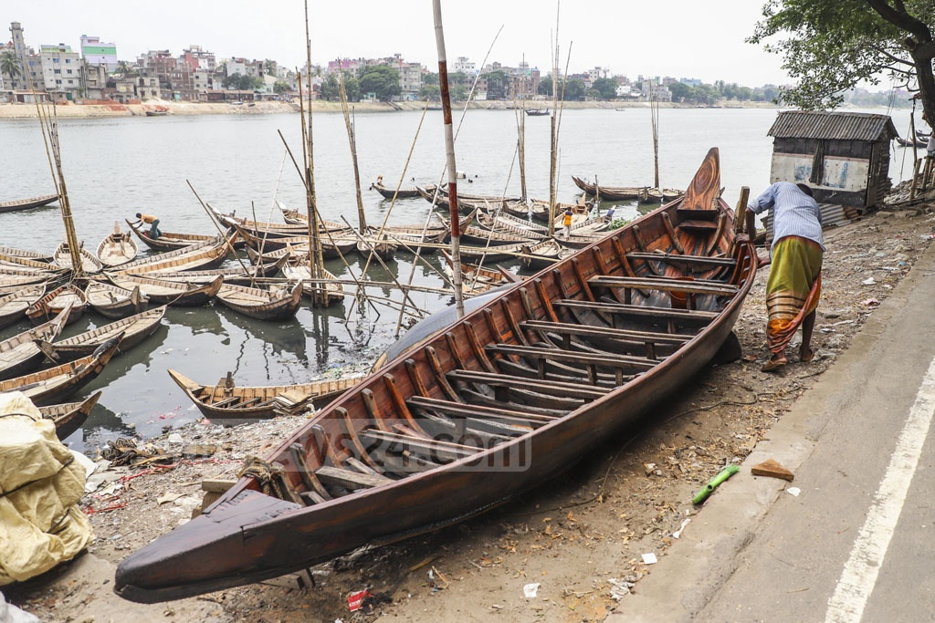 A man repairs his boat ahead of the monsoon season. This photo was taken at Dhaka's Kamrangirchar on Saturday. Photo: Abdullah Al Momin