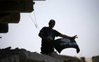 FILE PHOTO: A member of the Iraqi security forces celebrates as he holds an Islamic State flag on top of a building destroyed in clashes in the Old City of Mosul, Iraq Jul 10, 2017. REUTERS