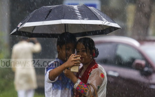A woman and her son taking a selfie to capture the moment of celebrating the first day of rainy season on the Bangla Academy premises in Dhaka on Saturday. Photo: Mostafigur Rahman