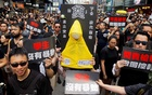 Protesters carry a yellow raincoat in memory of a man, who died after falling from a scaffolding at the Pacific Place complex while protesting, during a demonstration demanding Hong Kong's leaders to step down and withdraw the extradition bill, in Hong Kong, China, Jun 16, 2019. REUTERS