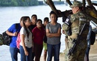 A member of naval police talks to people that crossed the Suchiate river on a raft from Tecun Uman in Guatemala to Ciudad Hidalgo, Mexico June 16, 2019. Reuters