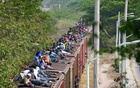 FILE PHOTO: Central American migrants, moving in a caravan through Juchitan, Oaxaca are pictured atop a train known as