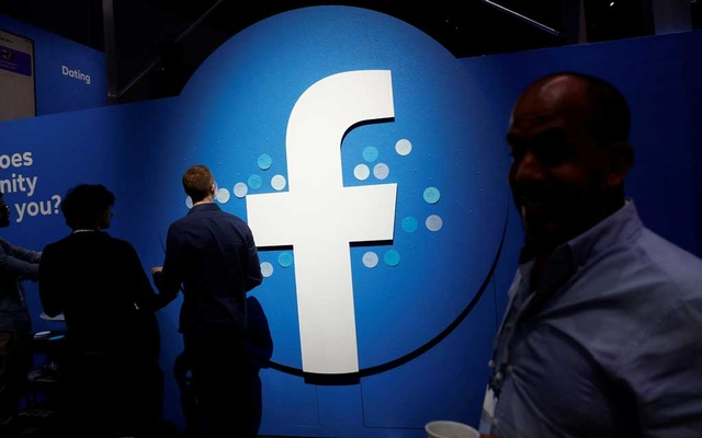 FILE PHOTO: Attendees walk past a Facebook logo during Facebook Inc's F8 developers conference in San Jose, California, United States, April 30, 2019. Reuters