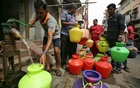 A man uses a hand-pump to fill up a container with drinking water as others wait in a queue on a street in Chennai, India, Jun 17, 2019. REUTERS
