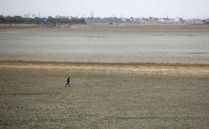 A man walks through the dried-up Puzhal reservoir, on the outskirts in Chennai, India, Jun 20, 2019. REUTERS