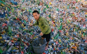 FILE PHOTO: A Vietnamese man works recycling plastic bottles at Xa Cau village, outside Hanoi, Vietnam Jun 5, 2018. REUTERS