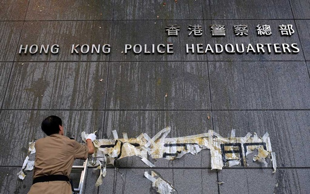 Staff try to clean off the marks from thrown eggs and anti-extradition graffiti on the walls of the Hong Kong Police headquarters in Hong Kong, China June 22, 2019. REUTERS
