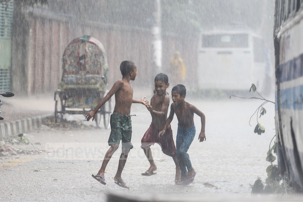Children enjoy moments in the rain at Dhaka's Mirpur-13, as the day brings a mixture of sunshine and rain. Photo: Asif Mahmud Ove