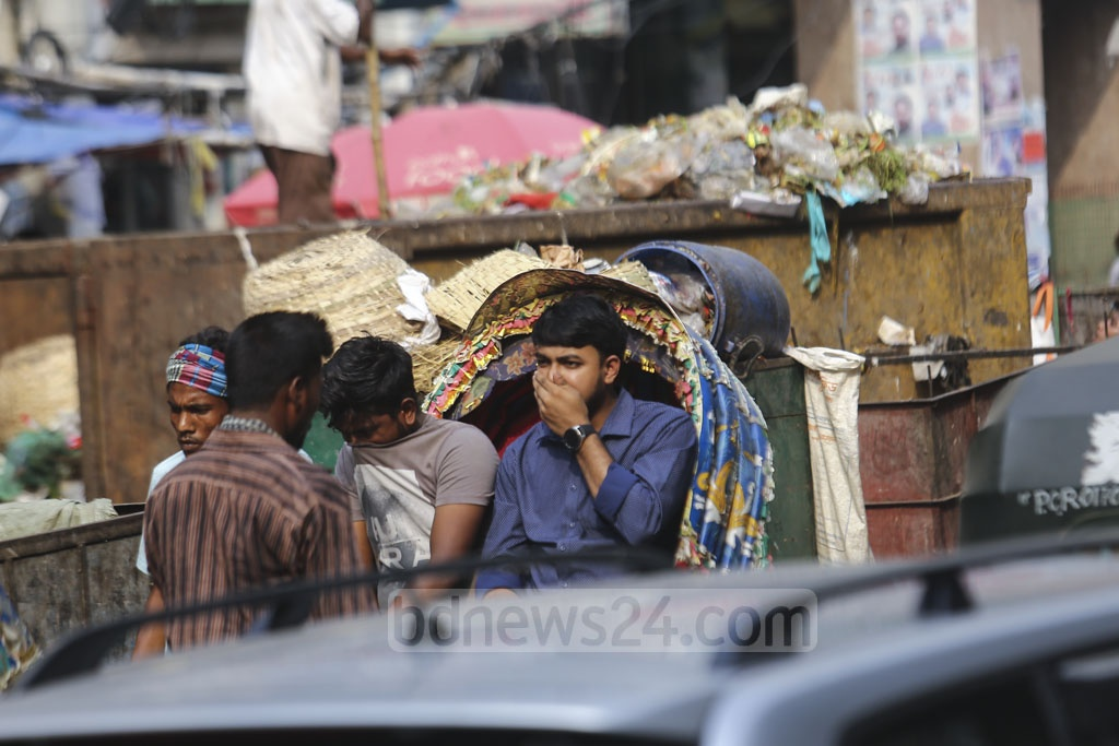 Two rickshaw riders cover their noses due to bad smells coming from a dustbin on the road at Dhaka's Moghbazar Wireless Gate. Photo: Mahmud Zaman Ovi