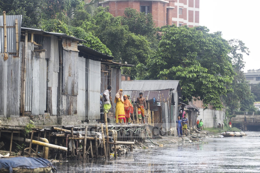 Clogged with wastes, water often overflows to the slum adjacent to Baganbari canal at Mirpur-14 in Dhaka, leading the residents to elevate the floors of their shanties using bamboos and wood. Photo: Asif Mahmud Ove