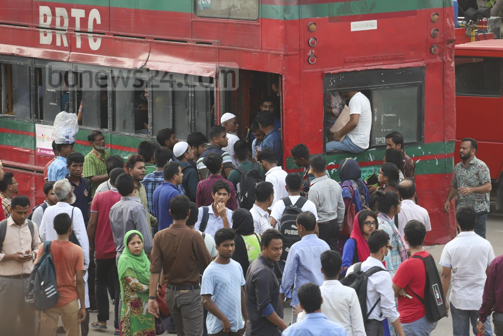 Commuters scramble to get on a bus as a lack of public transport triggers sufferings after office hours at Farmgate in Dhaka on Sunday. Photo: Abdullah Al Momin