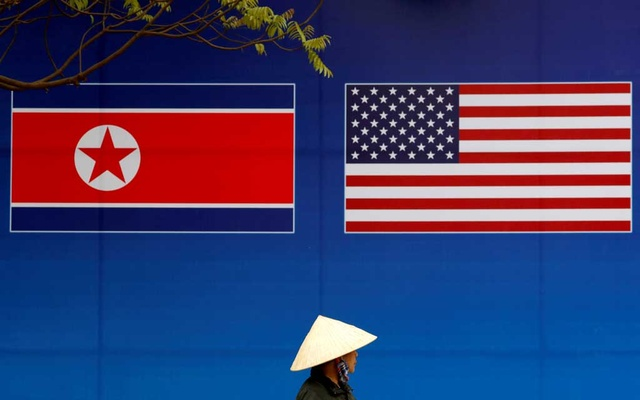 FILE PHOTO: A person walks past a banner showing North Korean and US flags ahead of the North Korea-US summit in Hanoi, Vietnam, Feb 25, 2019. REUTERS