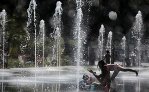 People cool off in a fountain in Nice as a heatwave hits much of the country, France, Jun 27, 2019. REUTERS