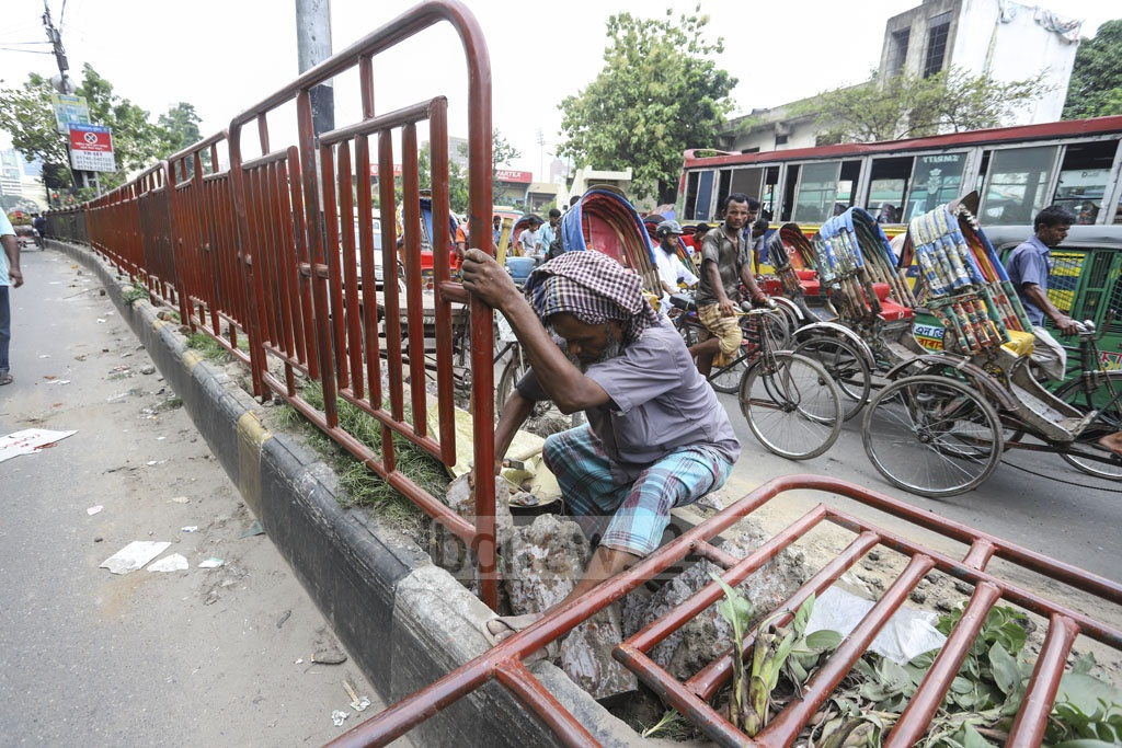 The authorities are setting up new fences on the divider along a street after dismantling the old ones in Dhaka's Gulistan on Saturday to stop jaywalkers from crossing the street, risking their lives. Photo: Asif Mahmud Ove