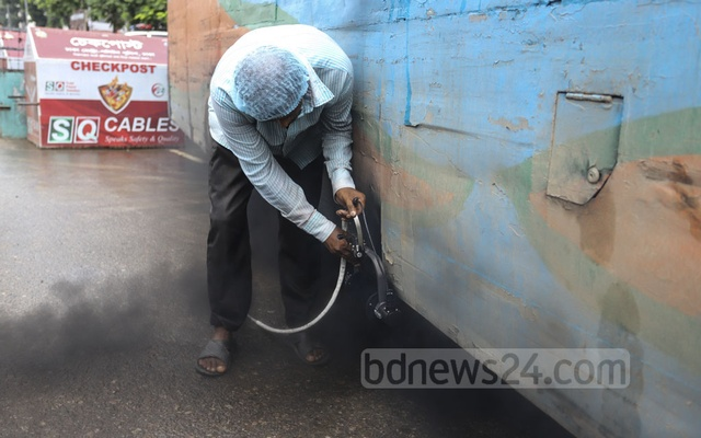 The Department of Environment workers checking whether black smoke emitted by a bus is at tolerable levels during a drive on Manik Mia Avenue in Dhaka on Sunday. Photo: Asif Mahmud Ove