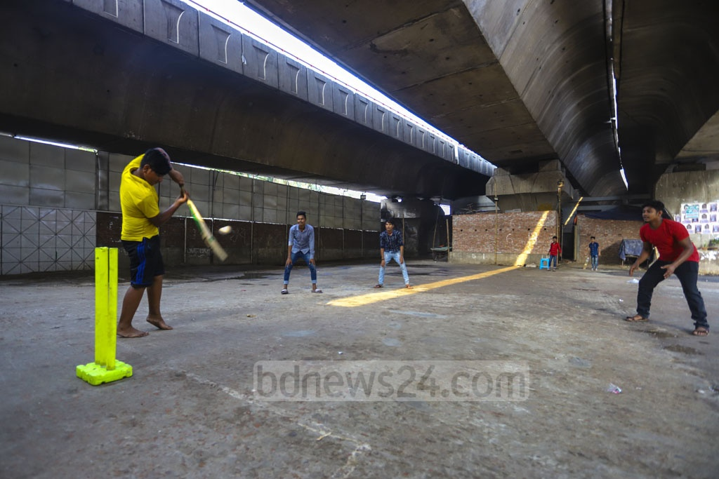 Boys play cricket on a strip of open space under the Mayor Hanif Flyover in Dhaka's Kaptan Bazar because of a shortage of playgrounds. Photo: Asif Mahmud Ove