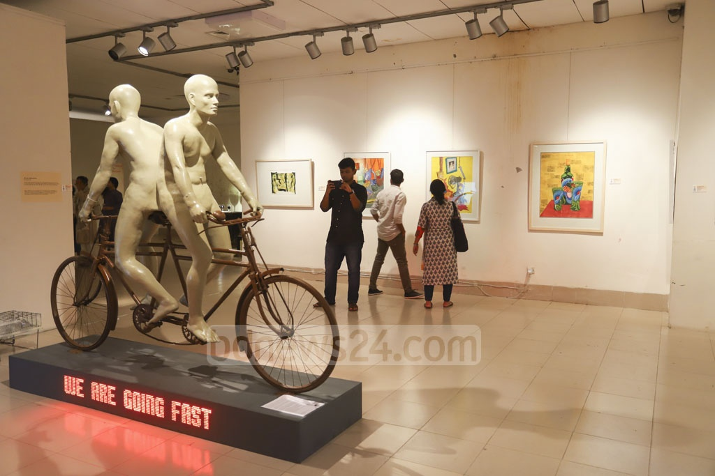 Visitors appreciate artworks at the 23rd Fine Arts Exhibition at the Shilpakala Academy in Dhaka on Tuesday. Photo: Asif Mahmud Ove