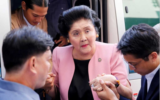 FILE PHOTO: Aides help former Philippine First Lady Imelda Marcos walk, as she arrives at an anti-corruption court Sandiganbayan, to attend a court hearing in Quezon City, Metro Manila, in Philippines Nov 16, 2018. REUTERS