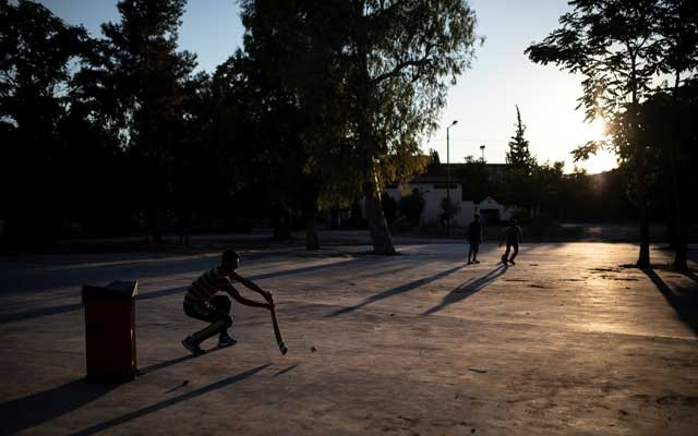 Pakistani men living in Greece play a game of tape-ball cricket in a parking lot in the Tavros neighbourhood in Athens, Greece, June 29, 2019. Reuters