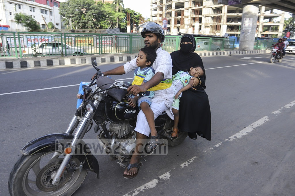 A man driving a motorcycle with a sleeping child tied up with himself while the pillion rider, a woman, holds another sleeping child in her lap. Only the driver is wearing a helmet. Photo: Asif Mahmud Ove