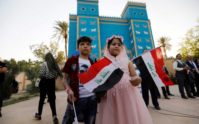 Children hold Iraqi flags during celebration after UNESCO designated ancient city of Babylon as World Heritage Site, in front of a replica of Ishtar gatee near Hilla, Iraq Jul 5, 2019. REUTERS