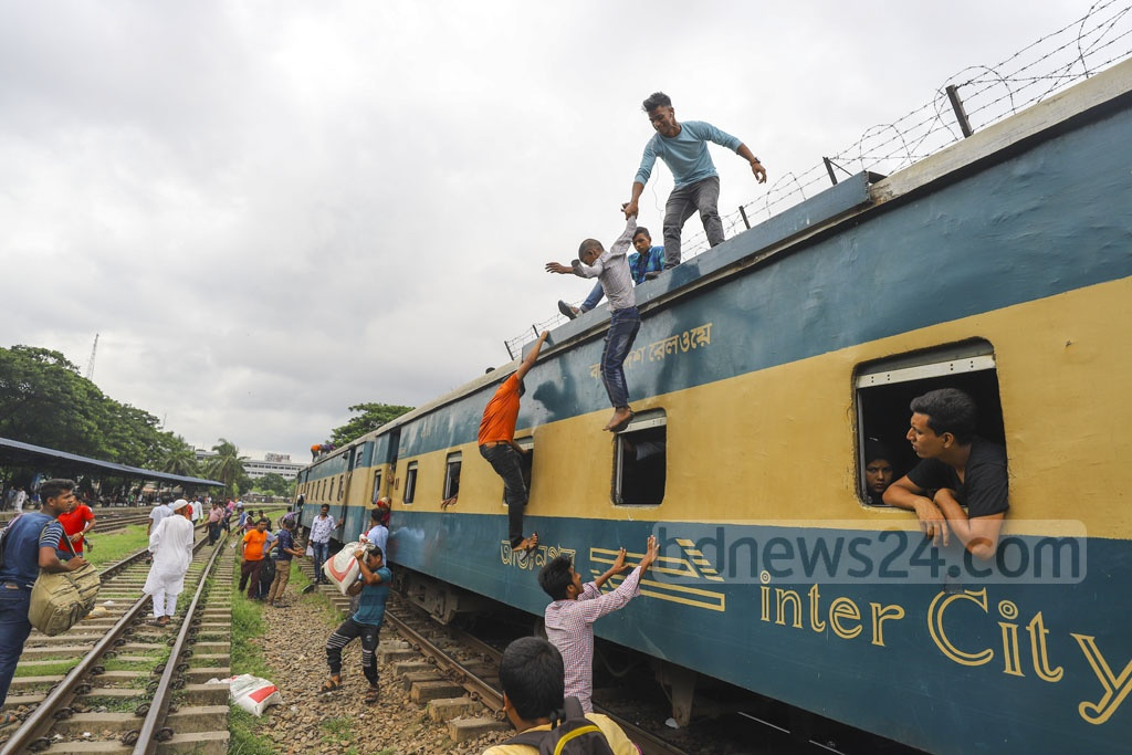Many people risk their lives by riding on the train rooftop or railings of engine to travel in Bangladesh even though the compartments have empty spaces. This photo was taken from Airport Railway Station in Dhaka on Saturday. Photo: Asif Mahmud Ove