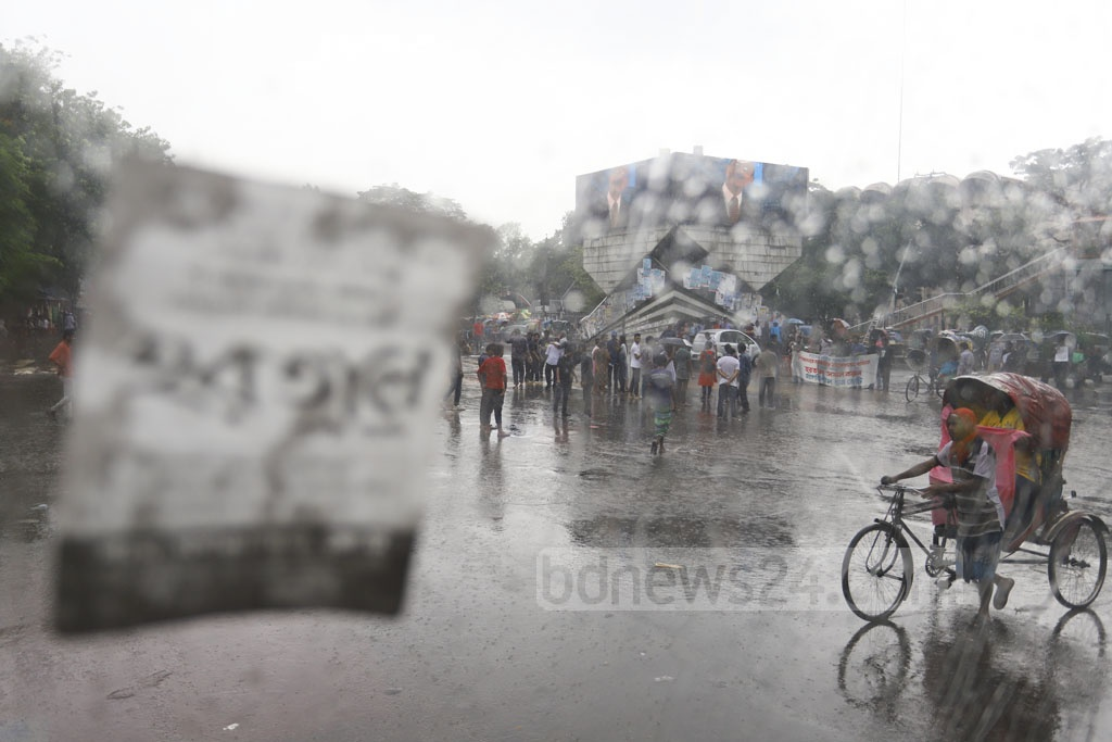 Activists of the Left Democratic Alliance brave rains to take control of Shahbagh intersection in Dhaka during the nationwide half-day general strike on Sunday in protest against a gas price hike. Photo: Asif Mahmud Ove